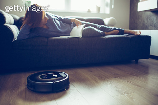 Woman reading book while robotic vacuum cleaner cleaning floor - gettyimageskorea