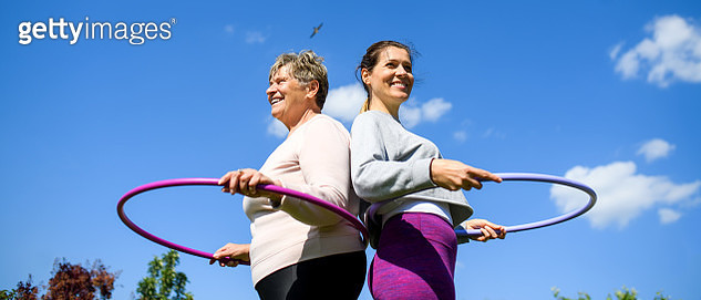 Low-angle view of woman with senior mother doing exercise outdoors. - gettyimageskorea