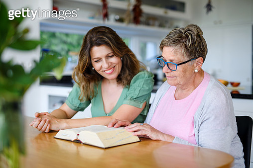 Portrait of woman with senior mother indoors at home, reading bible. - gettyimageskorea