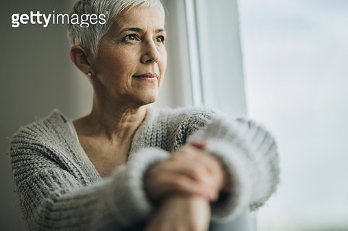 Portrait of beautiful mature woman relaxing by the window. - gettyimageskorea