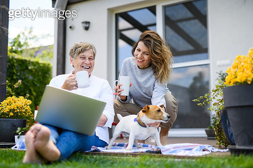 Woman with senior mother sitting outdoors, using technology. - gettyimageskorea