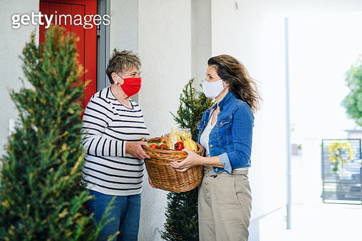 Woman with face mask bringing fruit and vegetables to senior mother, quarantine concept. - gettyimageskorea