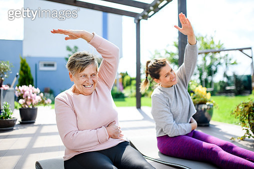 Portrait of woman with senior mother doing exercise on patio outdoors. - gettyimageskorea
