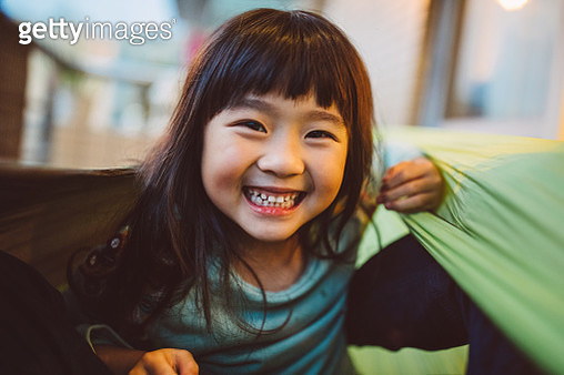 Lovely little girl smiling at the camera while playing joyfully in hammock - gettyimageskorea