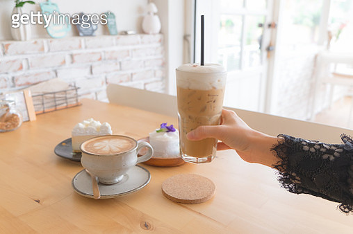 woman hand holding Ice coffee, hot coffee and cake on the wooden table in the coffee cafe. - gettyimageskorea