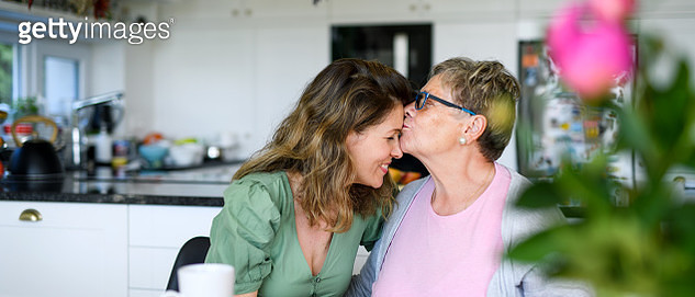 Senior mother kissing adult daughter on forehead indoors at home. - gettyimageskorea