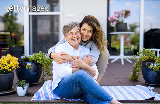 Portrait of woman with senior mother sitting outdoors, hugging. - gettyimageskorea