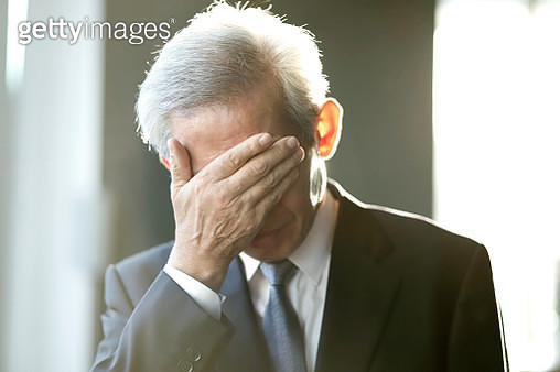 Senior businessman covering face with hand - gettyimageskorea