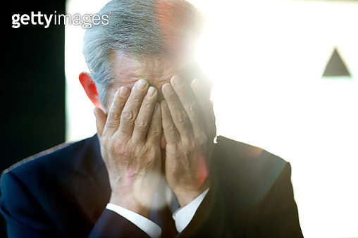 Senior businessman covering face with hands - gettyimageskorea