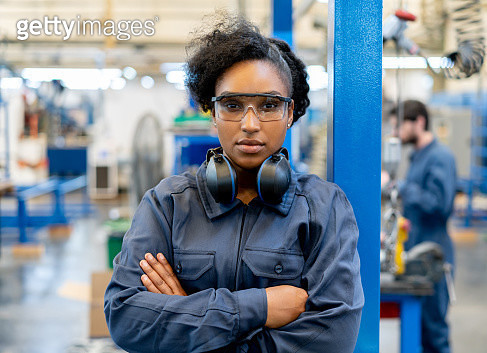 Black confident young woman working at a manufacturing factory wearing protective goggles looking at camera with arms crossed - gettyimageskorea