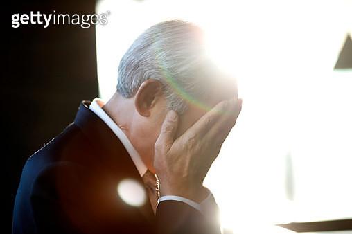 Senior businessman with hands over face - gettyimageskorea