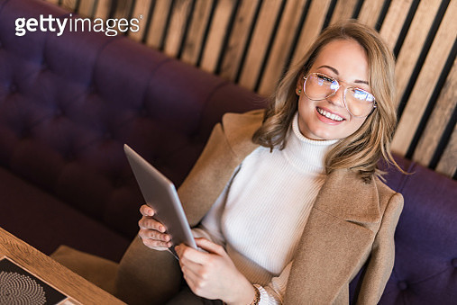 Cheerful young woman using a digital tablet while sitting in coffee shop. - gettyimageskorea