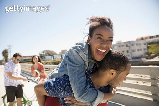 Playful couple piggybacking on sunny sidewalk - gettyimageskorea