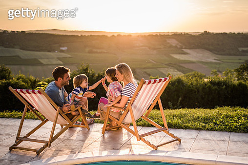 Happy family talking in deck chairs by the pool at sunset. - gettyimageskorea