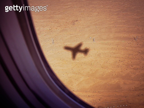 Shadow of airplane on desert ground - gettyimageskorea