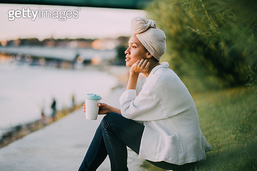 Muslim girl with a scarf having a cup of coffee by the river - gettyimageskorea