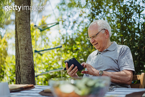 Senior Latin man is sitting in the yard and typing a message on smart phone. - gettyimageskorea