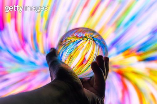 Holding a crystal ball through colorful background at night. - gettyimageskorea