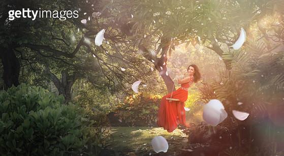 Woman swinging in jungle in red dress - gettyimageskorea