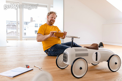 Happy man taking cell phone picture of toy car - gettyimageskorea