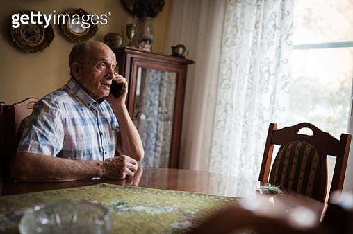 Cheerful senior man using mobile phone at home - gettyimageskorea