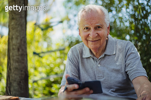 Portrait of senior Latin man sitting in the yard, holding smart phone and looking at camera. - gettyimageskorea