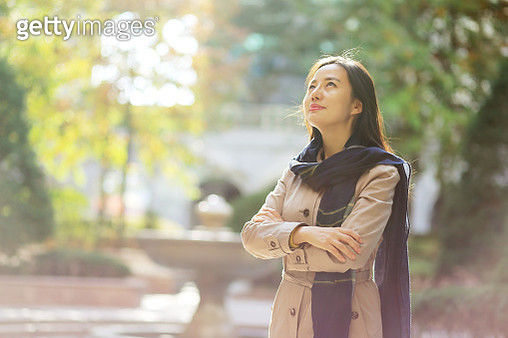 Woman standing with arms folded in autumn park - gettyimageskorea