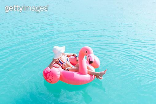 Woman on pink flamingo floating on sea - gettyimageskorea