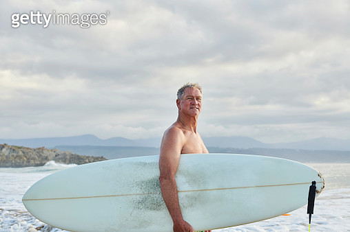 Older male surfer on beach looking at surf - gettyimageskorea
