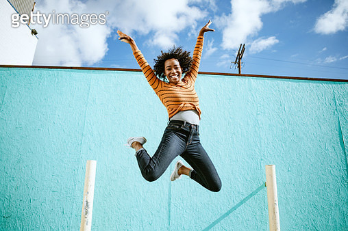 A beautiful African American woman smiles, jumping high in the air with her arms outstretched and a smile on her face.  Horizontal image with copy space.  Shot in Los Angeles, California. - gettyimageskorea