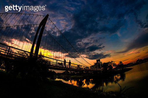 Silhouette Of Suspension Bridge Against Cloudy Sky - gettyimageskorea