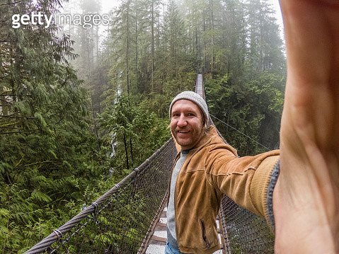 Man walking on suspension bridge crossing canyon in rainforest, river beside, Canada - gettyimageskorea