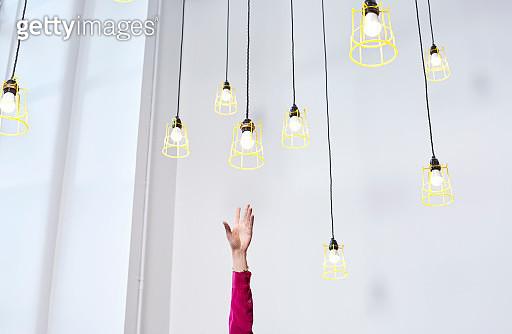 A hand reaching for conceptual idea lightbulbs - gettyimageskorea