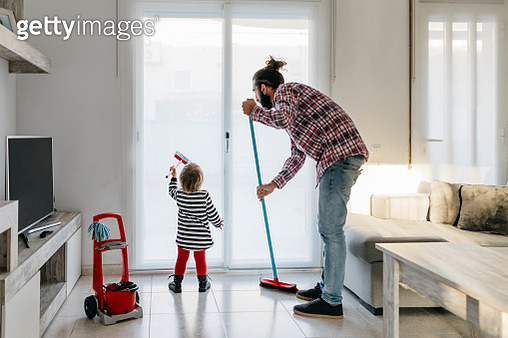 Father and little daughter cleaning the living room together - gettyimageskorea