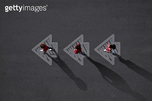 School children dressed in red, walking across painted arrows - gettyimageskorea