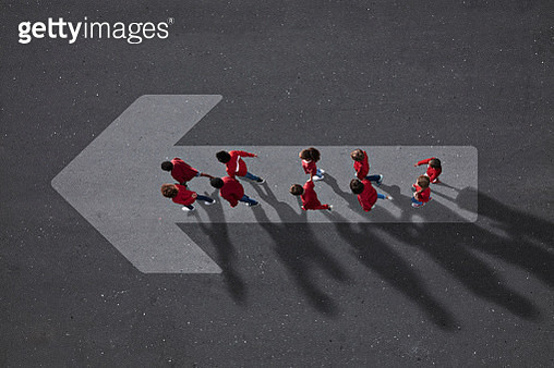 School children dressed in red, walking across big painted arrow - gettyimageskorea