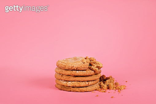 A short stack of homemade vegan, gluten-free peanut butter cookies on a pink background. Some of the cookies are crumbled. - gettyimageskorea