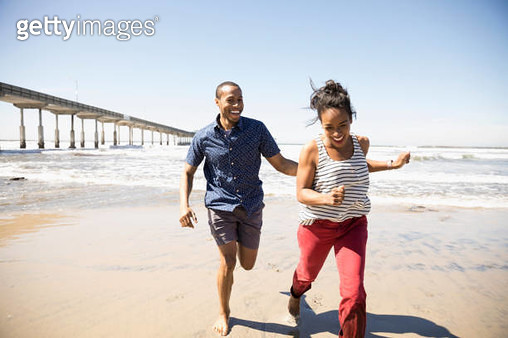 Playful couple running on sunny beach - gettyimageskorea