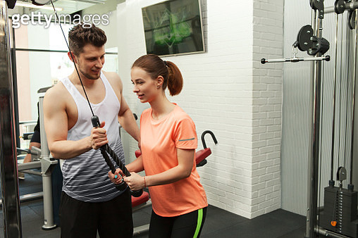 male coach helps a woman train in the gym - gettyimageskorea