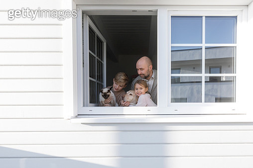 Father with his two children, dog and cat at opened window of their house - gettyimageskorea