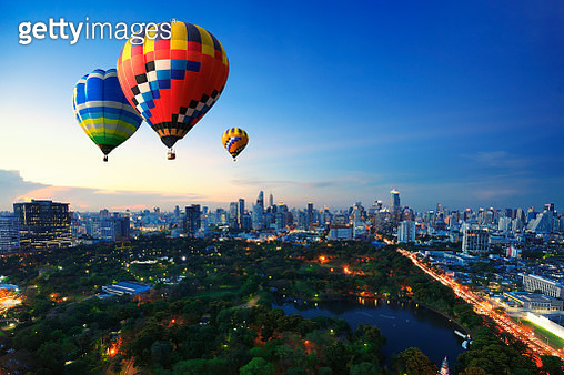 Hot air balloons fly over cityscape at sunset background - gettyimageskorea