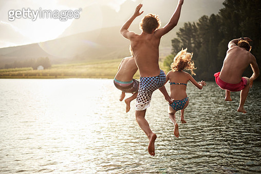 four friends jumping into a lake in the mountains - gettyimageskorea