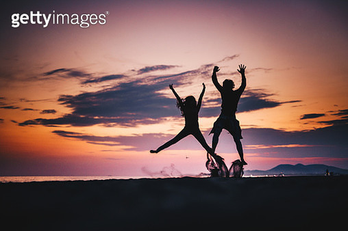 Silhouette of a couple jumping on the beach in the evening. - gettyimageskorea