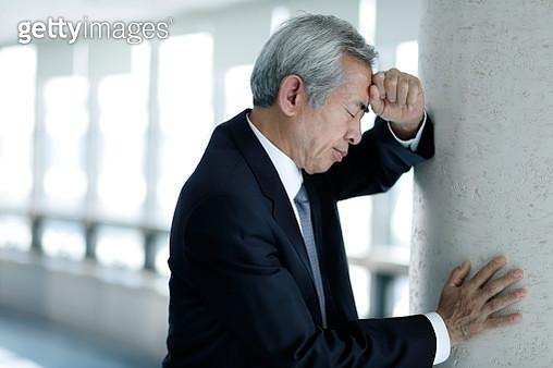 Tired senior businessman leaning against wall - gettyimageskorea