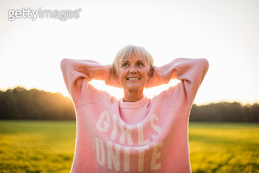 Portrait of confident senior woman standing on rural meadow at sunset - gettyimageskorea