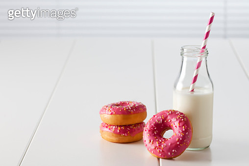 Glass bottle of milk and three doughnuts with pink icing on white ground - gettyimageskorea
