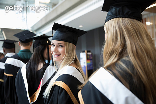 Portrait smiling, confident female college student graduate in cap and gown - gettyimageskorea