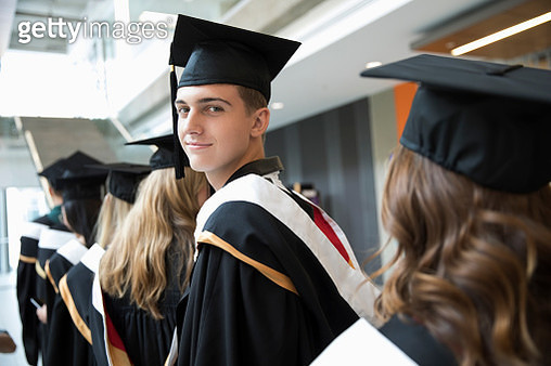 Portrait confident male college student in cap and gown - gettyimageskorea