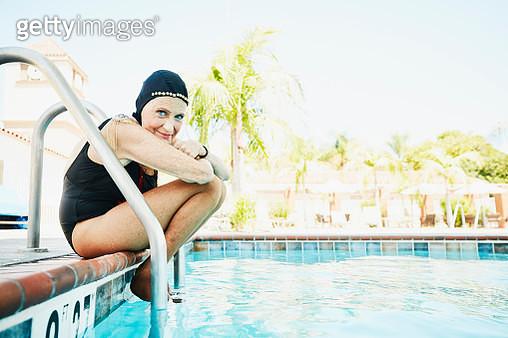Portrait of senior female synchronized swimmer sitting on edge of pool - gettyimageskorea