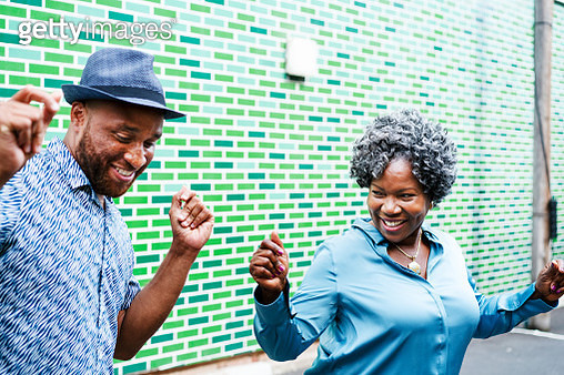 Man and woman dancing next to wall - gettyimageskorea